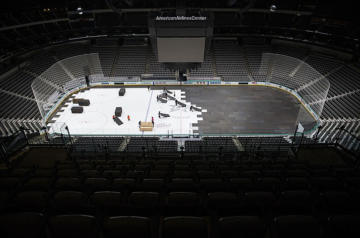 In this March 12, 2020, file photo, crews cover the ice at American Airlines Center in Dallas, home of the Dallas Stars hockey team, after the NHL season was put on hold due to the coronavirus.Hockey became the latest sport to finalize a return during a global pandemic after NHL owners and players approved an agreement Friday to resume the season. (Ashley Landis/The Dallas Morning News via AP, File)