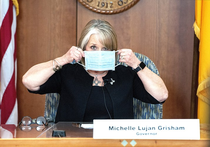 New Mexico Gov. Michelle Lujan Grisham puts on her face mask when not speaking during an update on the COVID-19 outbreak in the state during a news conference in the state Capitol in Santa Fe, N.M. Gov. Lujan Grisham used her line-item veto power to preserve executive control over hundreds of millions of dollars in federal coronavirus relief funding, a move that could mean the loss of additional financial assistance for some Native American communities. She used her veto pen to scratch out entire paragraphs of the budget to prevent the Legislature from earmarking $318 million in federal virus relief funding for local governments. (Eddie Moore/The Albuquerque Journal via AP, Pool, File)