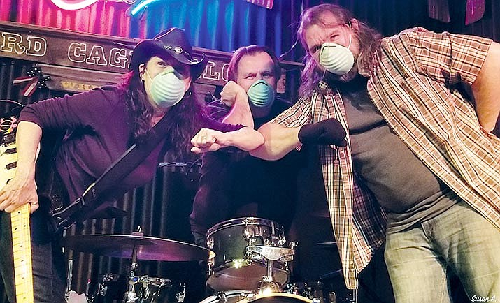 Llory McDonald, left, Darryl Icard and SteveBotterweg bump elbows. McDonald said that many musicians were getting back to their audiences before Gov. Doug Ducey's June 29 order closed most bars in Arizona.