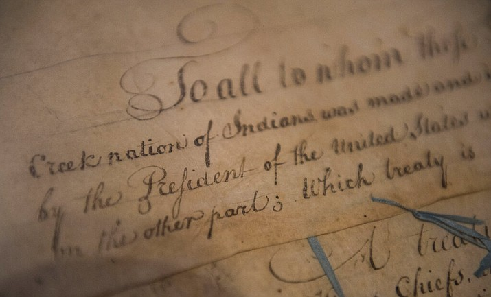 """FILE - This March 16, 2015, file photo, shows a detail of the 1790 Treaty of the Muscogee (Creek) Nations and the United States non display at the Smithsonian's National Museum of the American Indian """"Nation to Nation: Treaties Between the United States and American Indian Nations"""" in Washington. The Supreme Court has ruled Thursday, July 9, 2020, that Oklahoma prosecutors lack the authority to pursue criminal cases in a large chunk of eastern Oklahoma that remains an American Indian reservation. The case was argued by telephone in May because of the coronavirus pandemic. The case revolved around an appeal by a Native American man who claimed state courts had no authority to try him for a crime committed on reservation land that belongs to the Muscogee (Creek) Nation. (Kevin Wolf/AP Images for Smithsonian's National Museum of the American Indian, via AP, File)"""