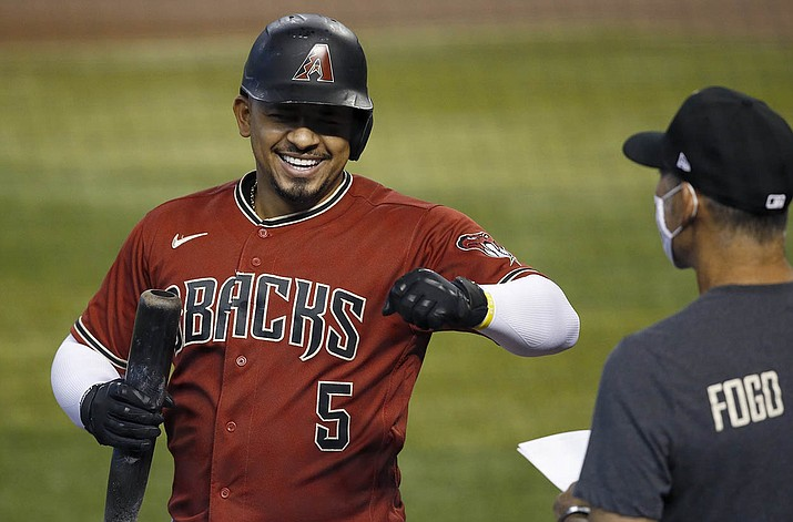Arizona Diamondbacks' Eduardo Escobar (5) smiles as he celebrates his home run with manager Torey Lovullo, right, during a baseball training camp intrasquad scrimmage Sunday, July 12, 2020, in Phoenix. (Ross D. Franklin/AP)