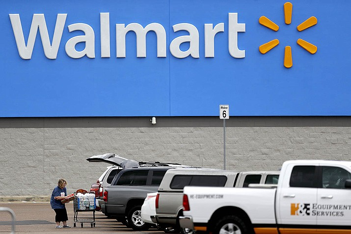 In this March 31, 2020 file photo, a woman pulls groceries from a cart to her vehicle outside of a Walmart store in Pearl, Miss. Walmart will require customers to wear face coverings at all of its namesake and Sam's Club stores. The company said the policy will go into effect on Monday, July 20, 2020 to allow time to inform stores and customers. (Julio Cortez, AP file)