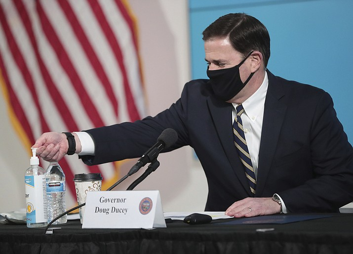 Arizona Gov. Doug Ducey uses hand sanitizer before updating reporters on COVID-19 in the state June 29, 2020, in Phoenix. The governor expects that Arizonans will need to continue to wear masks through at least the end of the year. (Michael Chow/The Arizona Republic via AP, Pool)