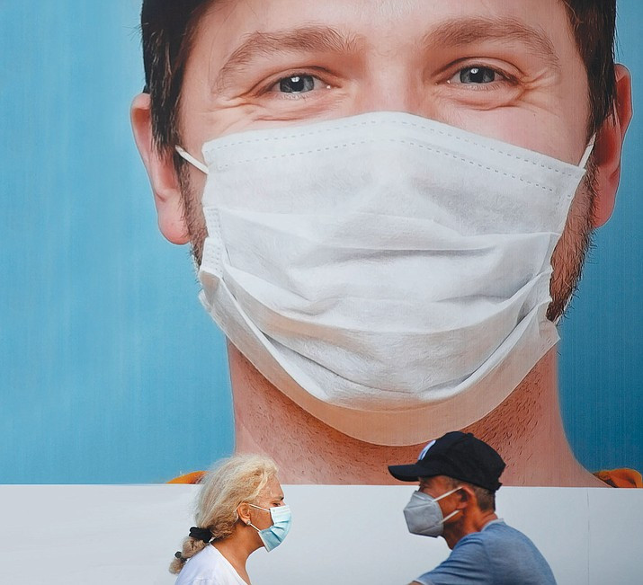 People wearing face masks walk by a billboard raising the awareness of wearing face masks following government measures to help stop the spread of the coronavirus Thursday, July 16, 2020. Businesses around the world, for lack of government intervention, have begun requiring face masks to contain the growing outbreak. (AP file photo)