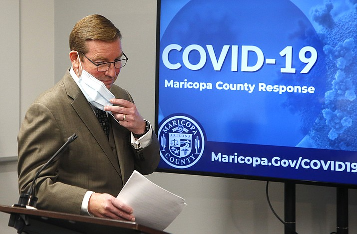Robert Rowley, director of the Maricopa County Emergency Management Department, removes his face covering as he steps up to the podium to talk about the ordering of storage containers with refrigeration units to handle the possible future surge in coronavirus cases, during a news conference Thursday, July 16, 2020, in Phoenix. The Maricopa County Medical Examiner's Office, which has already gotten four large portable storage coolers to handle future surges of coronavirus cases, has ordered another 10 coolers, which are expected to arrive by the end of next week. (AP Photo/Ross D. Franklin)