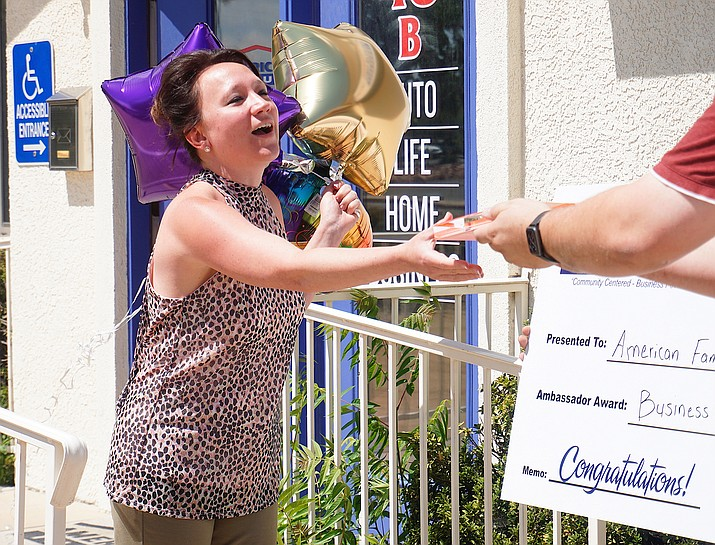 The Chino Valley Chamber of Commerce prize patrol gives the Business Leader Award to Leah McLemore of American Family Insurance in Chino Valley as part of a door-to-door, award-delivery event put on by the Chamber's Ambassador Program on Thursday, July 16, 2020. (Aaron Valdez/Review)