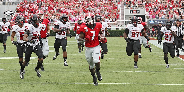 In this Saturday, Sept. 14, 2019, file photo, Georgia running back D'Andre Swift (7) scores on a pass play which he broke for a touchdown during the first half of an NCAA college football game against Arkansas State, in Athens, Ga. A team can go on the road and play a Power Five conference team and earn $1 million-$2 million, often enough to keep other sports programs afloat or fund the training table or academic center. (Bob Andres/Atlanta Journal-Constitution via AP, File)