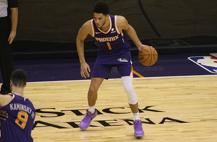 Devin Booker, right, and the Phoenix Suns are a longshot to land a playoff spot when the NBA season resumes on Thursday, July 30, 2020. (Miner file photo)