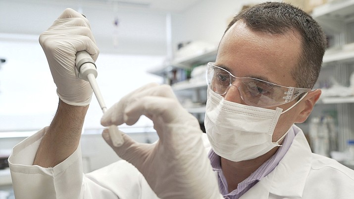 In this image from video provided by Washington University, researcher Nicolas Barthelemy works on a p-tau217 test for Alzheimer's disease at a laboratory in St. Louis, Mo., on Monday, July 27, 2020. Several companies and universities have developed versions of these tests, which look for a form of tau protein, one of the substances that can build up and damage the brains of people with Alzheimer's. (Huy Mach/Washington University, St. Louis via AP)