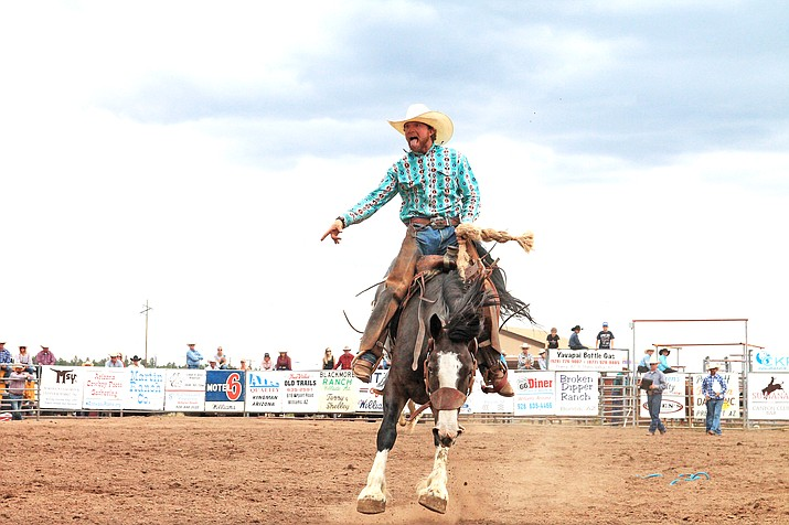 A bronc rider showboats for the crowd July 25 at the 42nd annual Cowpunchers Reunion Rodeo. (Loretta  McKenney/WGCN)