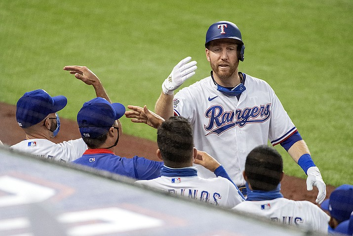 Texas Rangers' Todd Frazier celebrates with teammates after his solo home run off of Arizona Diamondbacks starting pitcher Madison Bumgarner during the fourth inning of a baseball game Wednesday, July 29, 2020, in Arlington, Texas. (Jeffrey McWhorter/AP)
