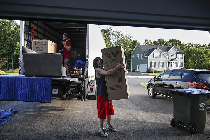 Movers unload a truckload of belongings as the Lilly family move into their new home, Tuesday, July 21, 2020, in Washingtonville, N.Y. New Yorkers anxious after weathering the worst of the coronavirus pandemic are fueling a boom in home sales and rentals around the picturesque towns and wooded hills to the north. Real estate brokers and agents describe a red-hot market recently, with many house hunters able to work from home. (John Minchillo/AP)
