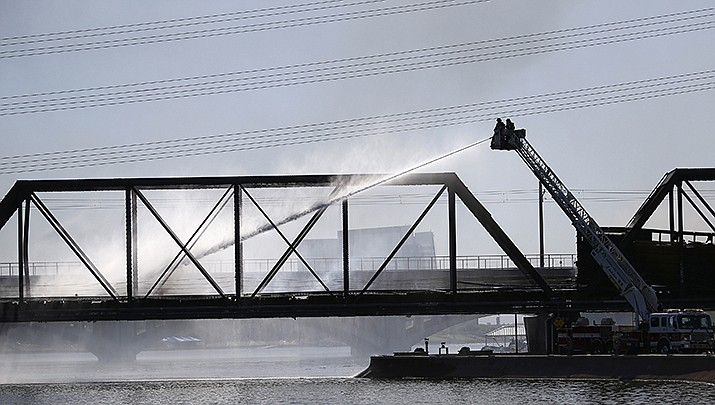 Local firefighters attempt to put out a fire on a derailed freight train on a bridge spanning Tempe Town Lake Wednesday, July 29, 2020, in Tempe, Ariz. (AP Photo/Ross D. Franklin)