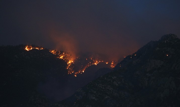 The Bighorn Fire moves along the western side of the Santa Catalina Mountains, Sunday, June 14, 2020, in Oro Valley, Ariz. Hundreds of homes on the outskirts of Tucson remain under an evacuation notice as firefighters work to keep the wildfire from moving downhill from canyons and ridges in the Coronado National Forest. (Ross D. Franklin/AP, file)