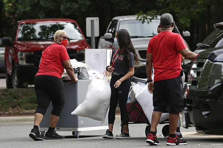 College students with the assistance of their families begin moving in for the fall semester at N.C. State University in Raleigh, N.C., Friday, July 31, 2020. The first wave of college students returning to their dorms aren't finding the typical mobs of students and parents. At N.C. State, the return of students was staggered over 10 days and students were greeted Friday by socially distant volunteers donning masks and face shields. (Gerry Broome/AP)
