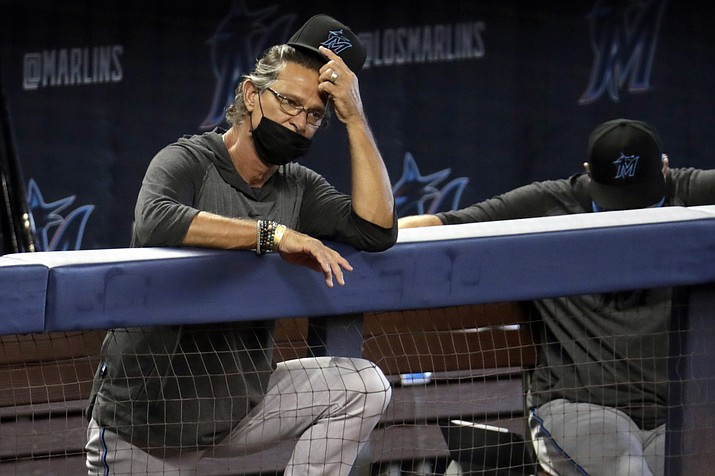 In this Sunday, July 12, 2020, file photo, Miami Marlins manager Don Mattingly watches a baseball scrimmage at Marlins Park in Miami. The Marlins, one of the most under-the-radar teams in sports, have making news lately, all of it bad. Overtaken by a coronavirus outbreak, the team must scramble for roster replacements as they try salvage a season barely underway. (Lynne Sladky/AP, file)