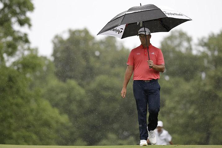Jon Rahm walks on the ninth fairway in the rain during the final round of the Memorial golf tournament Sunday, July 19, 2020, in Dublin, Ohio. (Darron Cummings/AP)