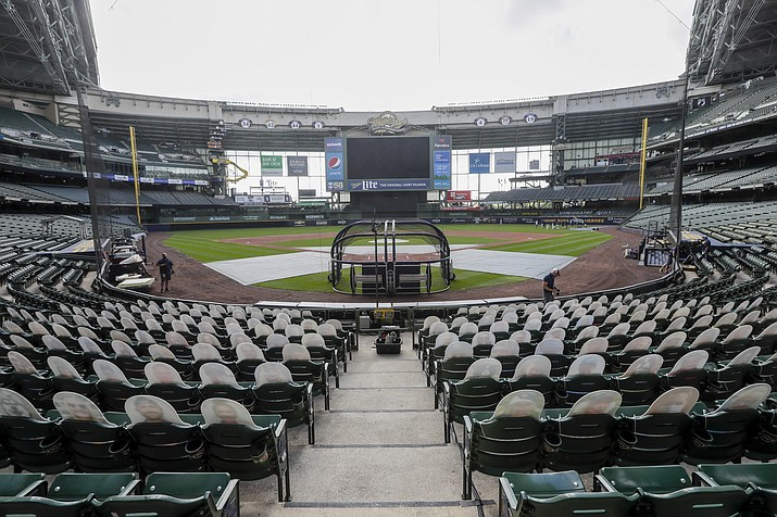 In this Friday, July 31, 2020 photo, fan cutouts sit in seats behind home plate at Miller Park after it was announced that the baseball game between the Milwaukee Brewers and Cardinals in Milwaukee, was postponed after two Cardinals employees tested positive for the coronavirus. (Morry Gash/AP, File)