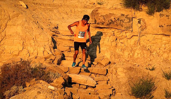 "A Louis Tewanima 10k Footrace runner navigates rugged steps on the Hopi course in a prior year, but COVID-19 this year forced a virtual race. Racers ""can run, jog, or walk on the road, on the trail, on the treadmill, at the gym, or on the track (or even at another race),"" the website says. (Photo courtesy of Sam Taylor)"