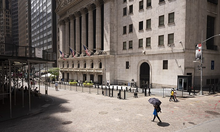 People pass the New York Stock Exchange, Thursday, July 30, 2020. Wall Street stalled on Friday, Aug. 7, as a whirlwind of worries about rising U.S-China tensions and whether Congress can deliver more aid for the economy threaten to halt its big run. (Mark Lennihan/AP, file)