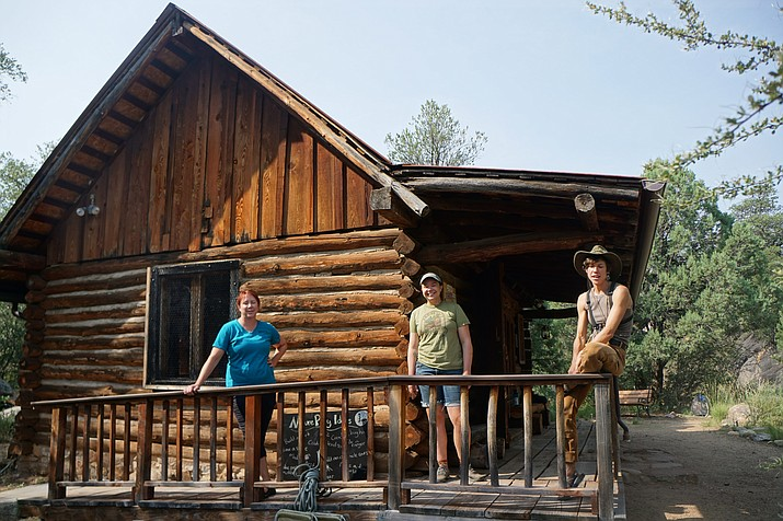 Prescott Recreation Coordinator Kelly Tolbert, left, AmeriCorps volunteer Taylor White, and Ellen Bashor, education director, stand in front of the cabin at the Community Nature Center, where Prescott Unified School District K-6 students will soon be able to do distance learning during the COVID-19 pandemic. (Cindy Barks/Courier)