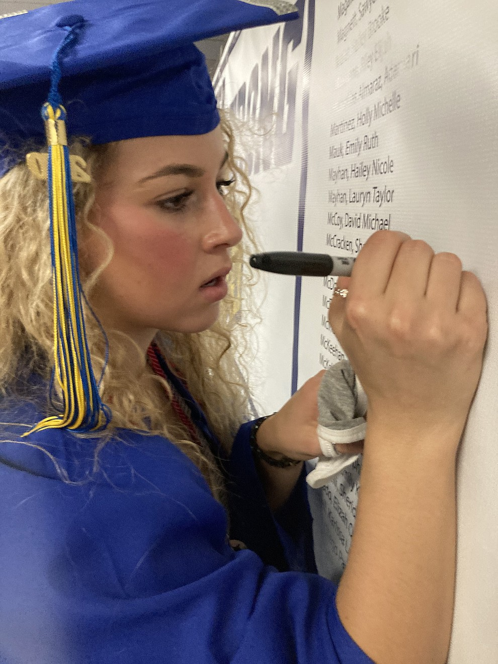 Prescott High School graduate Shannon McCracken writes her name on a graduate poster in the PDS lobby at the school's graduation Saturday, Aug. 8, 2020. (Nanci Hutson/Courier)
