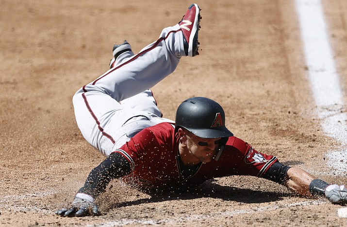 Arizona Diamondbacks' Nick Ahmed slides safely into home plate to score on a single hit by Ketel Marte off Colorado Rockies starting pitcher Antonio Senzatela in the fifth inning of a baseball game Wednesday, Aug. 12, 2020, in Denver. (David Zalubowski/AP)