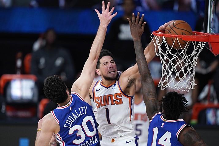 Phoenix Suns guard Devin Booker (1) makes a basket as Philadelphia 76ers guard Furkan Korkmaz (30) and forward Norvel Pelle (14) defend during the second half of an NBA basketball game Tuesday, Aug. 11, 2020, in Lake Buena Vista, Fla. (Ashley Landis/AP, pool)