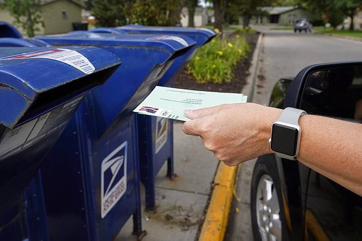 In this Tuesday, Aug. 18, 2020 photo, a person drops mail-in ballots into a mail box. (Courier file)