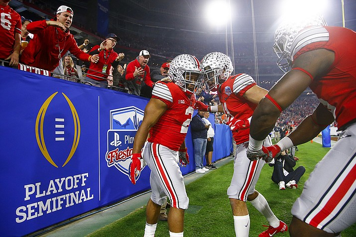 In this Dec. 28, 2019, file photo, Ohio State running back J.K. Dobbins, left, celebrates his touchdown with wide receiver Austin Mack during the first half of the team's Fiesta Bowl NCAA college football playoff semifinal against Clemson, in Glendale, Ariz. Clemson is preseason No. 1 in The Associated Press Top 25, Monday, Aug. 24, 2020, a poll featuring nine Big Ten and Pac-12 teams that gives a glimpse at what's already been taken from an uncertain college football fall by the pandemic. Ohio State was a close No. 2. (Ross D. Franklin, AP File)