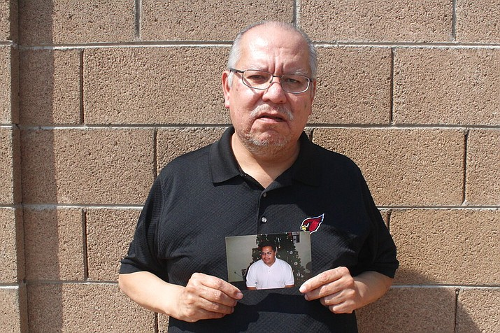 Auska Mitchell holds a photograph of his nephew, Lezmond Mitchell, on Friday, Aug. 21, 2020, in the Phoenix area. Lezmond Mitchell is scheduled to be executed Wednesday, Aug. 26, and the Navajo government is pushing to spare his life on the basis of cultural beliefs and sovereignty. (AP Photo/Jonathan J. Cooper)