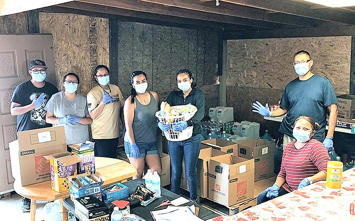 """Defend Our Community volunteers ready supplies for distribution to Navajo elders. """"Sometimes, it just feels like they're forgotten,"""" says Terrah Whitehair, fourth from the left. (Photo courtesy of Defend Our Community)"""