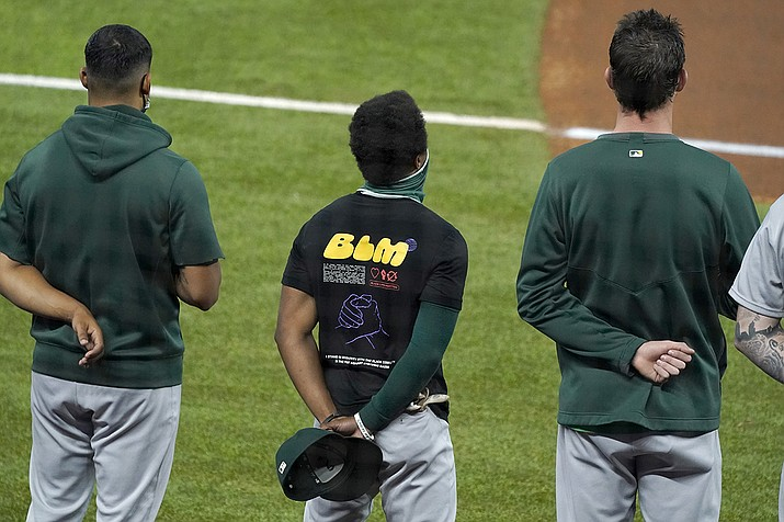 Oakland Athletics' Tony Kemp wears a Black Lives Matter shirt as he stands with his team during the playing of the national anthem before a baseball game against the Texas Rangers in Arlington, Texas, Wednesday Aug. 26, 2020. (AP Photo/Tony Gutierrez)