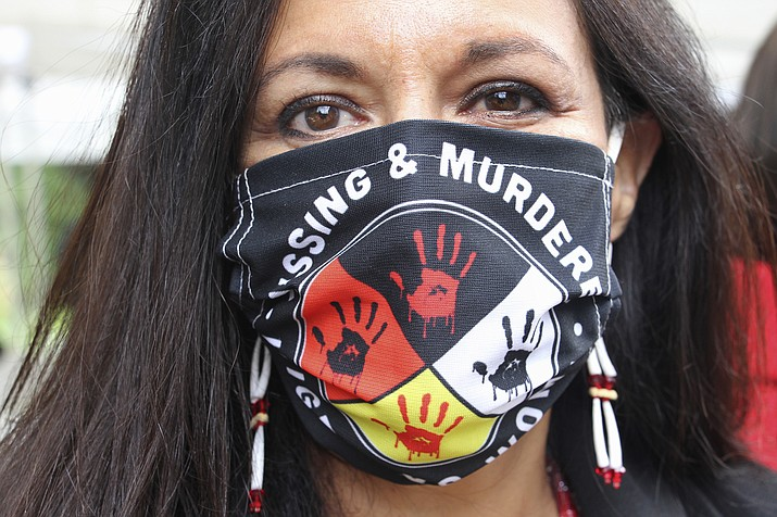 Jeannie Hovland, the deputy assistant secretary for Native American Affairs for the U.S. Department of Health and Human Services, poses with a Missing and Murdered Indigenous Women mask, Aug. 26 in Anchorage, Alaska. (AP Photo/Mark Thiessen)