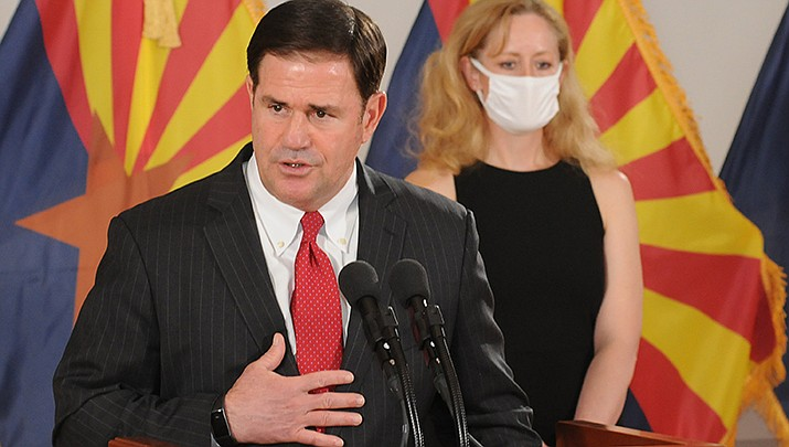 Arizona Gov. Doug Ducey stresses the importance of Arizonans getting flu shots during the coronavirus pandemic. State Health Director Dr. Cara Christ looks on during a press briefing on Monday, Aug. 31. (Photo by Howard Fischer/For the Miner)