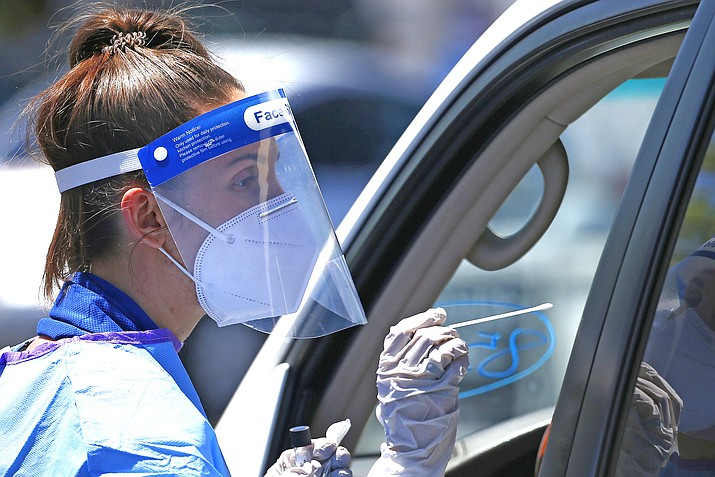 Dr. Sabrina Solt conducts coronavirus drive thru COVID-19 swab test in the parking lot at Impact Church May 4, 2020, in Scottsdale, Arizona. Free saliva based testing is available starting Sept. 2 in Flagstaff. (AP Photo/Ross D. Franklin)