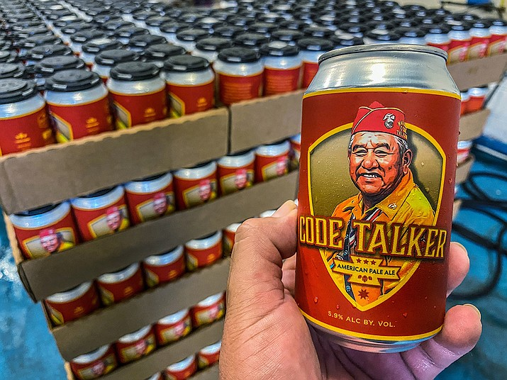 In this Aug. 14, 2020, photo courtesy of LT Goodluck, LT Goodluck holds a beer can honoring his grandfather, Navajo Code Talker John V. Goodluck at the Hellbender Brewing Co., in Washington, D.C. In honor of National Navajo Code Talkers Day the craft brewery recently rereleased its Code Talker American Pale Ale , this time in a can, drawing some rave reviews but also backlash. The beer was formulated and brewed by Goodluck in honor of his late grandfather and Navajo Code Talker John V. Goodluck. (LT Goodluck via AP)
