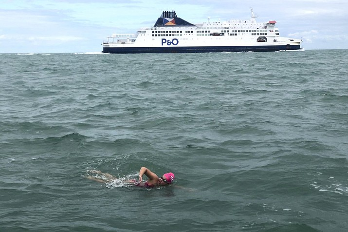In this photo provided by Darcie DeBlois-Rivard, long distance swimmer Vera Rivard, 16, of Springfield, N.H., below, swims the English Channel between Dover, England and Calais, France, as a channel ferry sails by, above, Tuesday, Sept. 1, 2020. The swim took her more than 14 hours, and she is the second American to cross the channel this year. (Photo Darcie DeBlois-Rivard via AP)