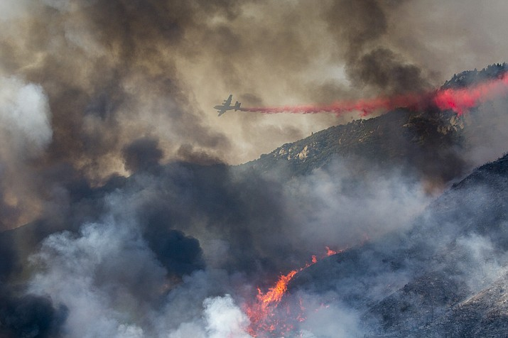 An air tanker drops retardant at a wildfire burns at a hillside in Yucaipa, Calif., Saturday, Sept. 5, 2020. Three fast-spreading wildfires sent people fleeing and trapped campers in one campground as a brutal heat wave pushed temperatures above 100 degrees in many parts of California. (Ringo H.W. Chiu/AP)