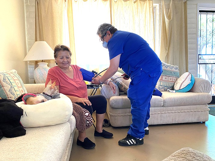In this May 15, 2020 photo provided by Shannon Todecheene her mother Carol Todecheene, left, receives therapy services at her daughter's home in Tucson, Arizona. Carol Todecheene was among those severely hit with the coronavirus. (Shannon Todecheene via AP)