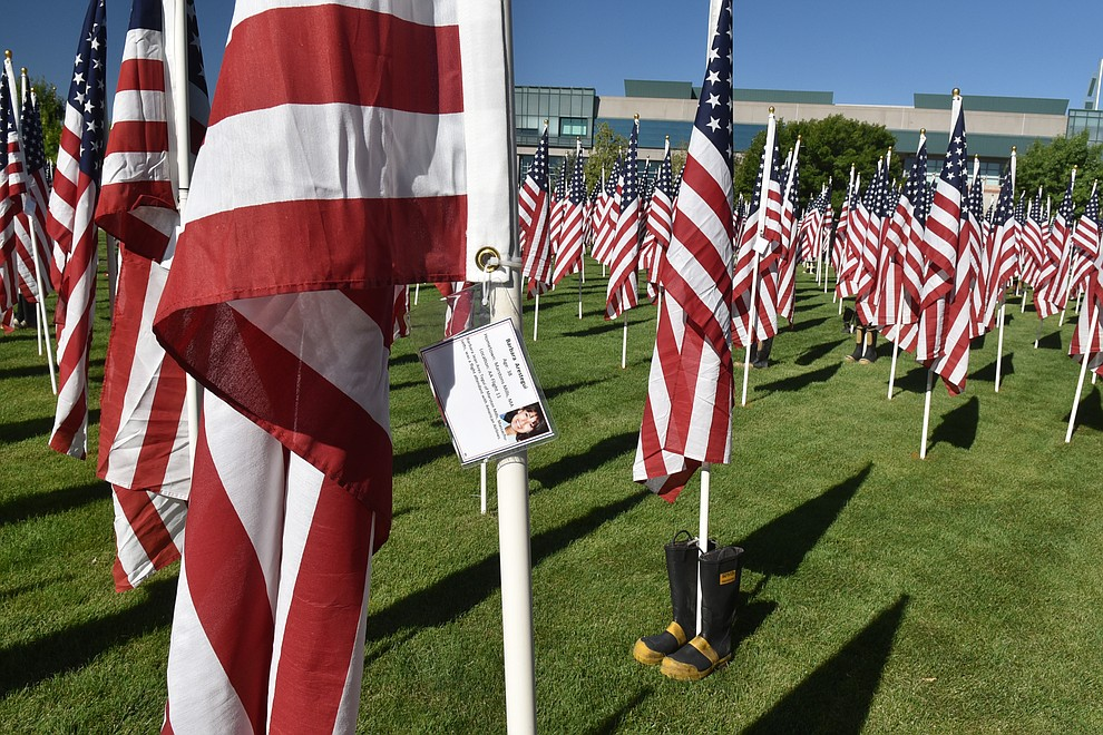 Each of the 3,000 flags has a tag identifying one of the victims of the 9/11 terrorist attacks. The boots at the base of a flagpole signifies that the victim was a firefighter, on Friday, Sept. 4, 2020. (Jesse Bertel/Courier).