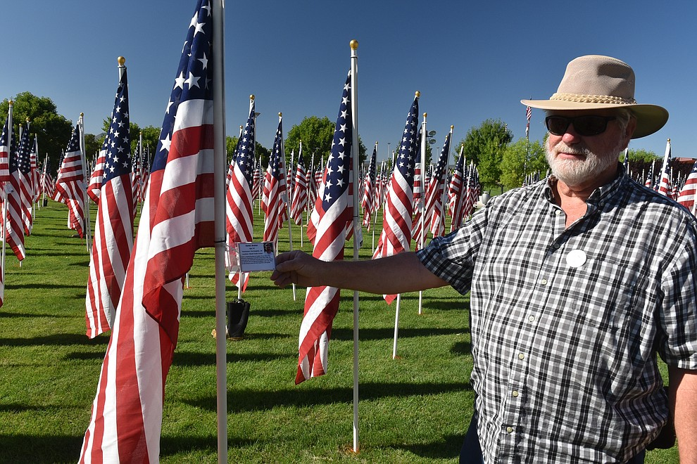 Healing Field volunteer Glen Sallie holds up one of the identifying tags on a flagpole, on Friday, Sept. 4, 2020. (Jesse Bertel/Courier).
