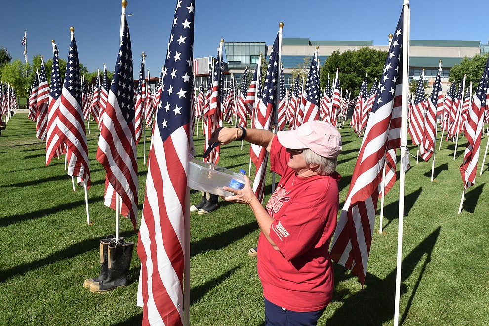 Healing Field volunteer Peggy Schmidt clips the excess plastic from zip ties that hold identifying tags to the flags, on Friday, Sept. 4, 2020. (Jesse Bertel/Courier).