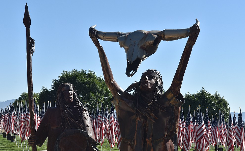 A statue of Native Americans in front of the Healing Field of commemorative flags, on Friday, Sept. 4, 2020. (Jesse Bertel/Courier).