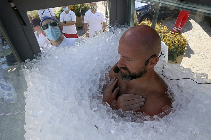 Austrian ice swimmer Josef Koeberl is standing in a glass cabin filled with ice try to break the world record for a human to stay side an ice box in Melk, Saturday, Sept. 5, 2020. (AP Photo/Ronald Zak)