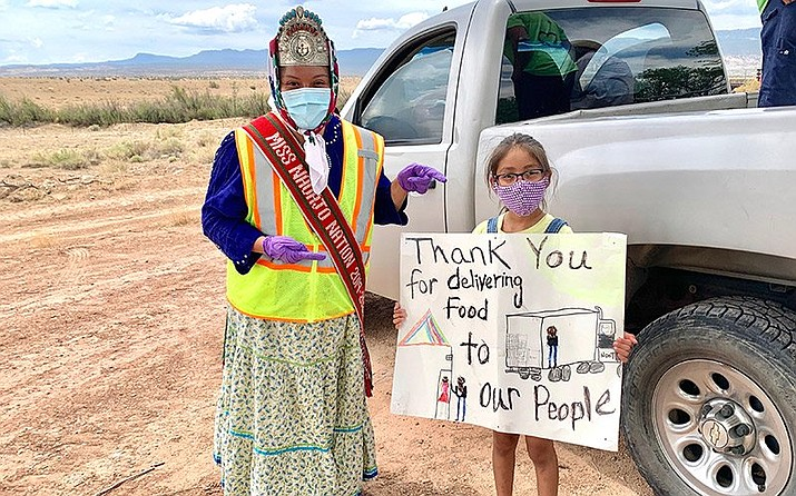 A child thanks Miss Navajo Nation Shaandiin Parrish for distribut-ing food, water and cleaning supplies in the Navajo communities of Gadi'i'á hi, Shiprock and Tse'Daa'Kaan during the COVID-19 pandemic June 12. (Photo courtesy of Shaandiin Parrish)