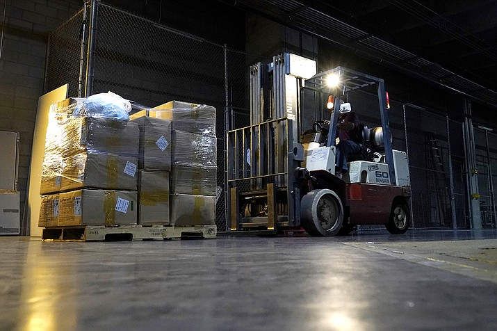 A worker picks up one of the dozens of pallets of more with one million pieces of PPE to help Phoenix schools reopen for the 2020-2021 school year fill a Phoenix Convention Center hall as the City of Phoenix begins to ship the pallets out to schools Sept. 8, 2020, in Phoenix. (AP Photo/Ross D. Franklin)