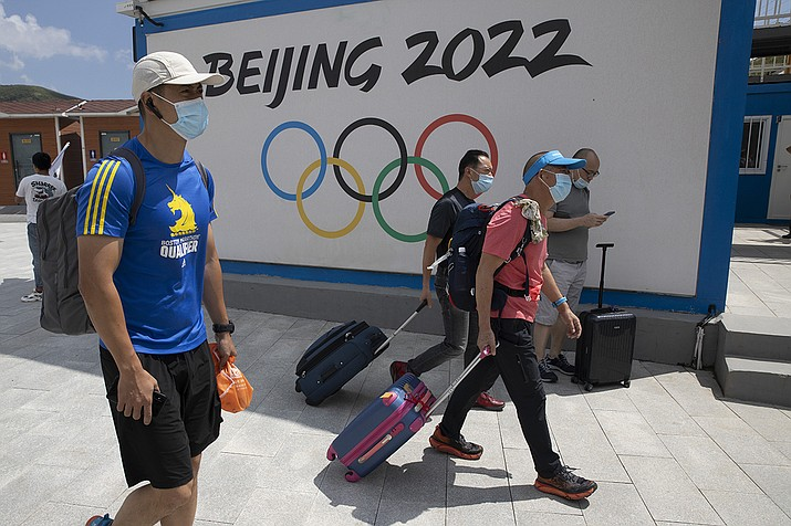 Visitors to Chongli, one of the venues for the Beijing 2022 Winter Olympics, past by the Olympics logo in Chongli in northern China's Hebei Province on Thursday, Aug. 13, 2020. China's repression in Tibet, the status of the exiled Dalai Lama, and its treatment of ethnic minorities spurred violent protests ahead of Beijing's 2008 Olympics. It could happen again. China is host to the 2022 Winter Olympics with rumblings of a boycott and calls to remove the games from Beijing because of widespread human rights violations. (Ng Han Guan/AP)