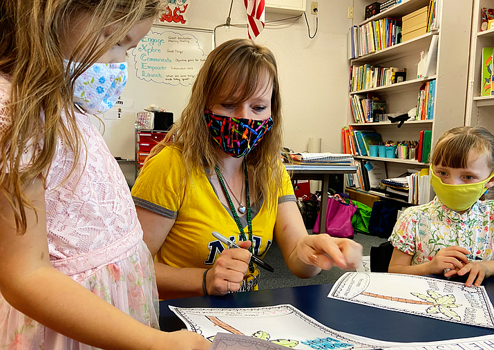 Lacey Coonfield, kindergarten teacher at Dr. Daniel Bright School in Cottonwood, helps Maya Adcock, left, and Chelsi Chezik with their coloring. Cottonwood-Oak Creek opened its schools Sept. 8-11 for the district's kindergarten through second grade students for a phased-in reopening before schools officially open on Sept. 14. VVN/Bill Helm
