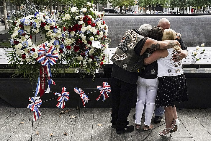 Mourners hug beside the names of the deceased Jesus Sanchez and Marianne MacFarlane at the National September 11 Memorial and Museum, Friday, Sept. 11, 2020, in New York. Americans commemorated 9/11 with tributes that have been altered by coronavirus precautions and woven into the presidential campaign. (John Minchillo/AP)